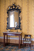 Ornate mirror and furniture in the Room of Conversation - Yellow Room in Palazzo Nicolaci di Valladorata, Noto, Sicily