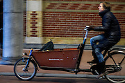 In Amsterdam rijdt een fietser op de bakfiets over het fietspad onder het Rijksmuseum.<br /> <br /> In Amsterdam a cyclist with a cargo bike is riding on the bike lane onderneath the Rijksmuseum.