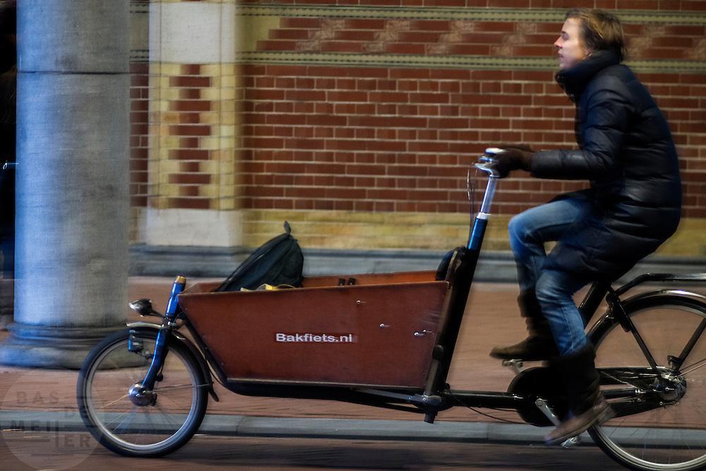 In Amsterdam rijdt een fietser op de bakfiets over het fietspad onder het Rijksmuseum.<br /> <br /> In Amsterdam a cyclist with a cargo bike is riding on the bike lane onderneath the Rijksmuseum.