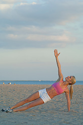 woman exercising and doing yoga by the sea