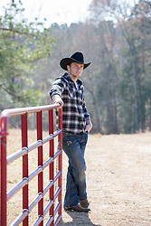 cowboy leaning on a ranch gate