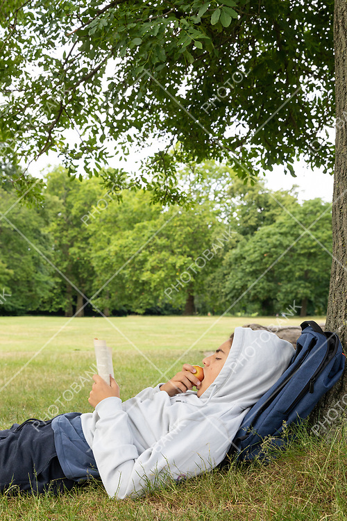 Young boy reads a book and eats an apple at the park leaning against the tree