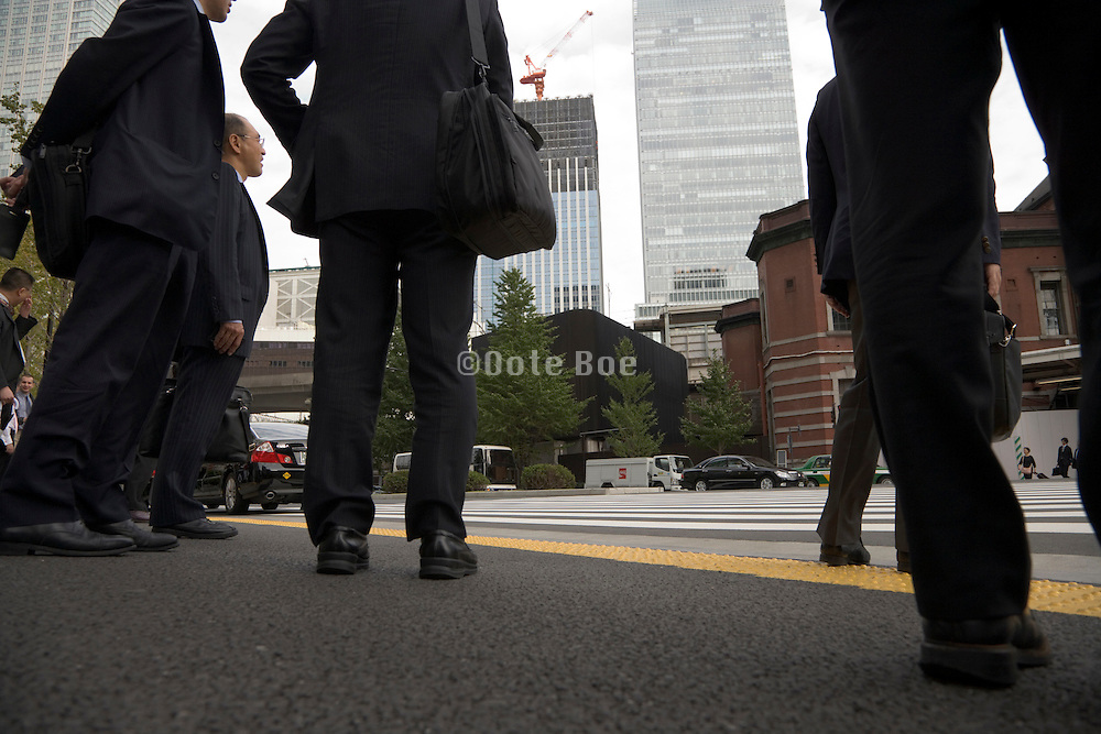 businesspeople waiting at a zebra crossing for light to get green