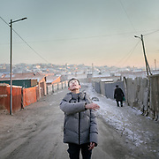 After school, a boy plays basketball in teh street. Based in a depression, the Bayankhoshuu ger district is one of the most polluted in Ulan Bator.<br />