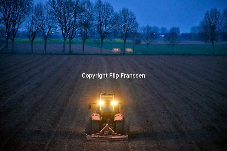 Nederland, Pannerden, 4-4-2020  Boer is tot diep in de avond bezig met zijn trekker de grond te bewerken. Foto: Flip Franssen