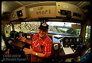 Conductor Jim Collins gabs in cab of Union Pacific #9501 as train races west along Columbia River. Oregon