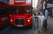 A couple reach out to touch an iconic but ageing red London Routemaster bus, on 18th April 2002, on Oxford Street, London, England.