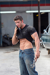 very good looking muscular auto mechanic wiping grease and dirt from his face with his tee shirt