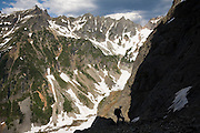 Climber Brian Polagye, standing in silhouette below East Wilmans Spire, looks out across Glacier Basin and the Monte Cristo Range in Mount Baker-Snoqualmie National Forest, Cascade Range, Washington on July 11, 2009.