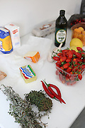 fresh tomatoes, herbs, butter and flour on a work table in a kitchen