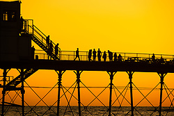 ©Licensed to London News Pictures. 13/09/2019 Aberystwyth UK. <br /> People standing on Aberystwyth's Victorian seaside pier are silhouetted as they watch the last rays of the suns as it sets over Cardigan Bay, on a glorious early autumn evening, The weekend is expected tp be warm and settled with temperatures in the mind 20's Celsius in parts of 5the south east of the UK. Photo credit Keith Morris/LNP