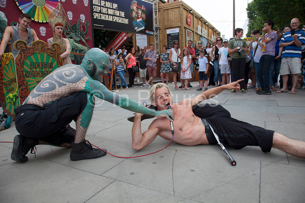Members from the London Wonderground sideshow freakshow perform a free show to entice in customers. The Lizard Man introduces the acts and sells the show 'on the inside' as a performer squeezes his whole body through a tennis racket. The South Bank is a significant arts and entertainment district, and home to an endless list of activities for Londoners, visitors and tourists alike.