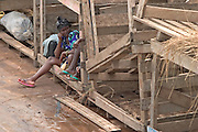 Women sitting in wooden crates aboard the Yapei Queen, the only passenger ferry on Lake Volta, the world's largest man-made lake.