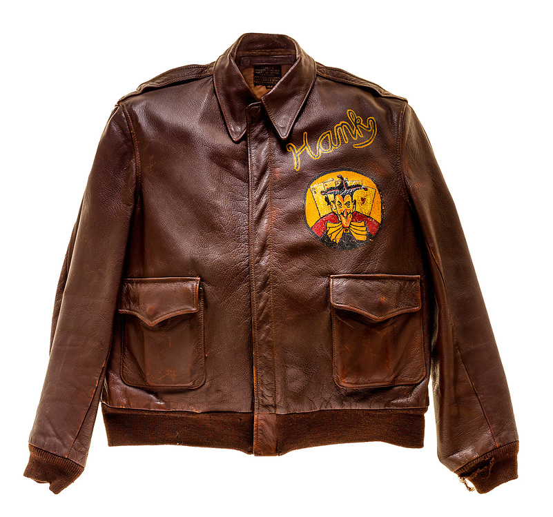 """Harry K. Senior, a co-pilot on the """"G.I. Wonder"""", wore this type A2 flight jacket. The 570th squadron patch is attached to the front of the jacket. Painted above the squadron patch is the name """"Hank"""", this is likely a nickname that Harry went by. The name of the aircraft he flew, """"G.I. Wonder"""", is painted on the back. The name of the city of Chester, PA is painted on the bottom of the back of the jacket."""