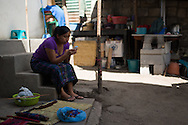 Estela Perez checks her mobile on the steps of her family home in Santa Catarina, Guatemala. Estela, her sisters, mother and grandmother create clothing and support their family by selling their wares to tourists.
