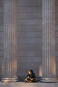 A young man sits cross-legged to read his book beneath the tall columns of the Bank of England on Threadneedle Street in the heart of the City of London, the capital's financial district, on 27th February 2021, in London, England.