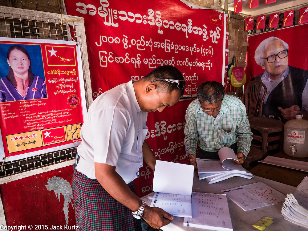 02 NOVEMBER 2015 - YANGON, MYANMAR: A Burmese voter (left) looks for his name on a list of voters at a NLD campaign outreach office in Mingaladon, a township in Yangon. Voter registration rolls were released Monday. Voters and party officials are double checking rolls to ensure accuracy.  National elections are scheduled for Sunday Nov. 8. The two principal parties are the National League for Democracy (NLD), the party of democracy icon and Nobel Peace Prize winner Aung San Suu Kyi, and the ruling Union Solidarity and Development Party (USDP), led by incumbent President Thein Sein. There are more than 30 parties campaigning for national and local offices.     PHOTO BY JACK KURTZ