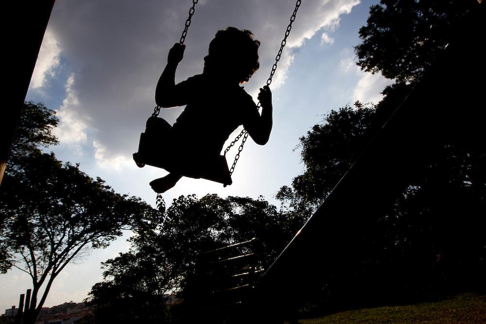 Betim_MG, Brasil.<br /> <br /> Silhueta de uma crianca brincando no balanco em no Projeto Escola da Gente em Betim, Minas Gerais.<br /> <br /> Silhouette of a child playing on the swing  in Escola da Gente Project in Betim, Minas Gerais.<br /> <br /> Foto: MARCUS DESIMONI / NITRO
