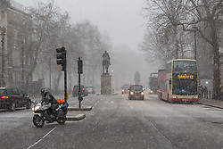 A motorcyclist carefully navigates a slippery Whitehall as a snow flurry hits Westminster at Horseguards. Westminster, London, February 27 2018.
