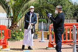 © Licensed to London News Pictures. 20/07/2020. London, UK. A worshipper wearing a face covering arrives at Wightman Road Mosque, also known as London Islamic Cultural Society and Mosque, in north London as the Mosque reopens for Zuhr (the afternoon prayer) after almost four months of lockdown. Last month the government announced that gatherings of more than 30 worshippers are allowed for acts of communal worship in churches, synagogues, mosques, temples and other places of worship. All worshippers attending Mosques have to wear face coverings and bring their own prayer mat, Quran, and a reusable shoe bag. Photo credit: Dinendra Haria/LNP