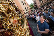 Huge crowds pay homage to the passage of a float depicting scenes from the Passion of Christ. Seville, Spain.