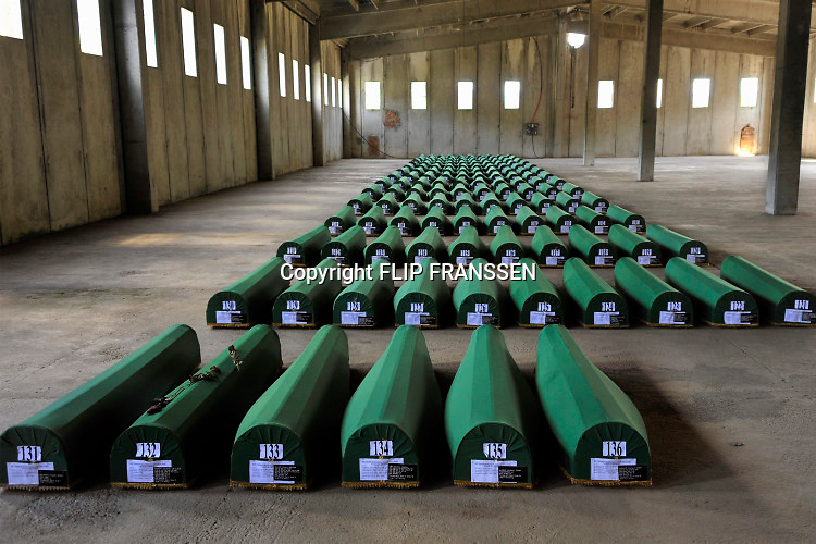 Bosnie, Potocari / Srebrenica, 11-7-2015 Nabestaanden nemen afscheid van de resten van hun geliefden in de voormalige dutchbatbasis, waar 136 kisten met stoffelijke resten klaar lagen om morgen begraven te worden tijdens de herdenking van de massamoord door de Serviers 20 jaar geleden. Hand, handen op een kist, doodskist, kistje, met de vlag van bosnie . Annual gathering at Potocari burial site of Srebrenica massacre. Srebrenica genocide was the killing of more than 8000 Bosniaks, mainly men and boys around the town of Srebrenica during the Bosnian War.Foto: ANP/ Hollandse Hoogte/ Flip Franssen