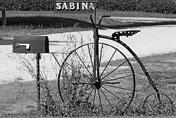 23 August 2013:   An antique high wheel bicycle holds the town sign next to a mailbox in Sabina Illinois.