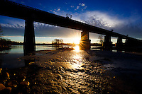 The sun sets under the railway bridge that crosses the Bow River through Refinery Park in SE Calgary.<br /> <br /> ©2015, Sean Phillips<br /> http://www.RiverwoodPhotography.com