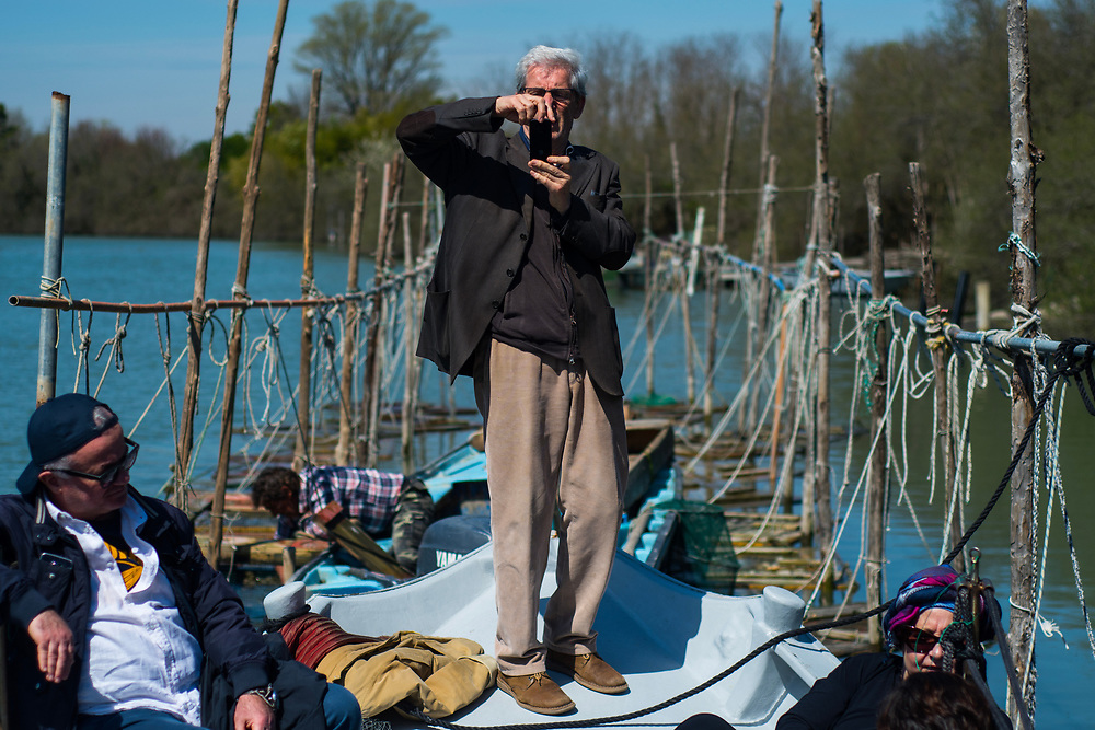 """VENICE, ITALY - APRIL 2018. <br /> A tourist takes a picture during the visit to Emiliano's """"cason"""", the typical temporary house of the fishermen in the Venetian lagoon, where he keeps the """"vieri"""", wooden boxes where the fisherman check the state of the crabs, during the fishing tour of the moeche."""