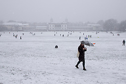 © Licensed to London News Pictures. 24/01/2021. London, UK. A woman uses an umbrella to shelter from snow exercise in Greenwich park, South East London. Snow is expected for large parts of the UK and a yellow weather warning is in place in parts of England. Photo credit: George Cracknell Wright/LNP