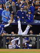 Oct 14, 2014; Kansas City, MO, USA; Kansas City Royals third baseman Mike Moustakas falls into fans in the stands as he catches a foul pop up hit by Baltimore Orioles center fielder Adam Jones (not pictured) during the sixth inning in game three of the 2014 ALCS playoff baseball game at Kauffman Stadium. Mandatory Credit: Peter G. Aiken-USA TODAY Sports