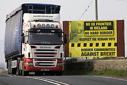 © London News Pictures. 28/03/2017. A lorry crosses the border from the Irish Republic to Northern Ireland close to an anti Brexit billboard, Wednesday 28th, March, 2017. Britian's Prime Minister Theresa May will trigger Article 50 tomorrow (Weds). Photo credit: Paul McErlane/LNP