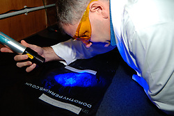 Forensic police officer searches for fingerprints on a plastic bag as evidence Yorkshire UK