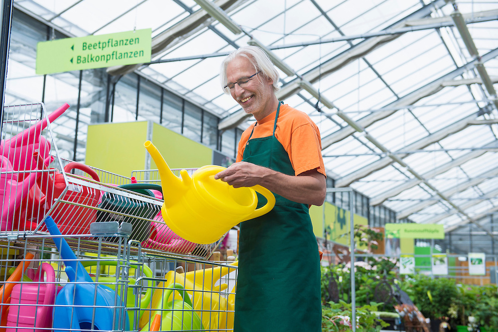 Male gardener arranging colourful watering cans, Augsburg, Bavaria, Germany