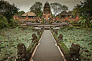 A walkway between lotus ponds leads visitors to a temple gate in the town of Ubud on Bali, Indonesia
