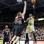 UCF Knights guard Isaiah Sykes (3) drives between Louisville Cardinals forward Montrezl Harrell (24) and Louisville Cardinals forward Stephan Van Treese (44) during an NCAA basketball game between the 14th ranked Louisville Cardinals and the UCF Knights at the CFE Arena on Tuesday, December 31, 2013 in Orlando, Florida. (AP Photo/Alex Menendez)