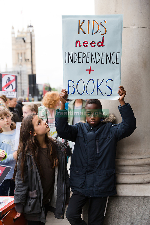 """July 24, 2017 - London, London, UK - LONDON, UK. Primary school children from Barnet take part in a """"Don't lock us out of our library"""" protest outside the offices of the Department for Culture, Media and Sport in Westminster, delivering 440 postcards addressed to Karen Bradley, the Culture Secretary, demanding a reinstatement of independent access to libraries. Public libraries in Barnet have been shut and are now reopening with restricted access and opening hours, making the service less accessible to vulnerable members of the community. (Credit Image: © Vickie Flores/London News Pictures via ZUMA Wire)"""