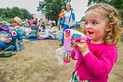 A young girl enjoys her first go with her bubble gun - The 2017 Latitude Festival, Henham Park. Suffolk 15 July 2017