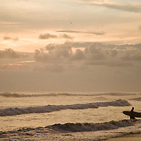 Surfers at sunset in Dominical, Costa Rica. April 2009. (Photo/William Byrne Drumm)