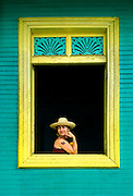 Portrait of a local woman framed in the window of a colonial Spanish house in San Juan del Sur, Nicaragua.
