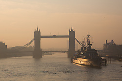 © Licensed to London News Pictures. 01/*04/2014. London, UK. Low level smog is seen in London this morning, 1st April 2014 during sunrise over Tower Bridge and the River Thames. High levels of pollution and poor air quality are forecast today and tomorrow believed in part to be caused by Saharan dust currently being deposited in the UK. Photo credit : Vickie Flores/LNP