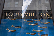 Luxury accessories brand, Louis Vuitton's logo and window design featuring golden swimming fish is seen in the window of the company's Cornhill premises, on 21st August 2020, in London, England.