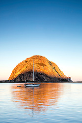 The first light of day casts a warm light on Morro Rock, Morro Rock in turn, casts a reflection upon the water of the harbor.