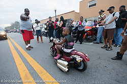 """A young rider parades down Dr. Mary McLeod Bethune Blvd on her """"starter Harley"""" during the annual """"Biking on the Boulevard"""" event during Daytona Beach Bike Week 2015. FL, USA. Saturday, March 14, 2015.  Photography ©2015 Michael Lichter."""