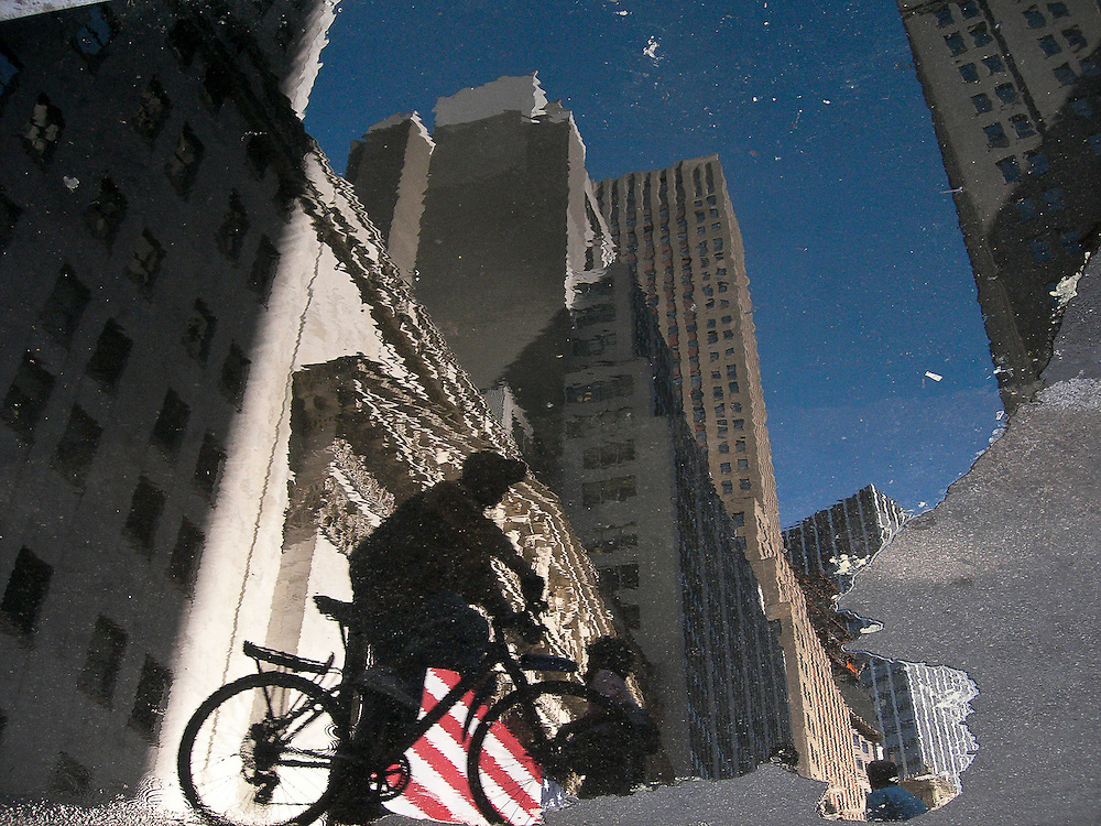 Reflection in a puddle of a biker riding in front of the New York Stock Exchange in Wall Street, Manhattan, New York, 2008.