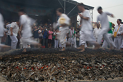 © Licensed to London News Pictures. 21/10/2015 Ipoh, Malaysia. Devotees walk over a bed of hot embers to purify their souls during a fire-walking ceremony on the last day of the Nine Emperor Gods Festival at Tow Boh Keong temple in Ipoh, Malaysia, Wednesday, Oct. 21, 2015. The festival is a nine-day Taoist celebration to mark the birth of the Nine Emperor Gods from the first day to the ninth day of the ninth moon in Chinese Lunar Calender. The origin of the Nine Emperor Gods (stars of the Northern constellation) can be traced back to the Taoist worship of the Northern constellation during Qin and Han Dynasty and absorb this practice of worshipping the stars and began to deitify them as Gods. Photo credit : Sang Tan/LNP