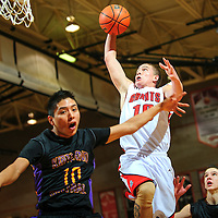 011113  Adron Gardner<br /> <br /> Grants Pirate Jacob Wilcox (10) attempts a layup ahead of Kirtland Central Bronco Asim Johnson (10) at Gallup High School Friday.