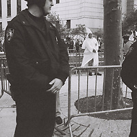 1. When was this photo taken?<br /> <br /> October 1999<br /> <br /> 2. Where was this photo taken?<br /> <br /> In Foley Square in lower Manhattan<br /> <br /> 3. Who took this photo<br /> <br /> I did<br /> <br /> 4. What are we looking at here?<br /> <br /> This picture was taken at a demonstration by 18 Ku Klux Klan members who gathered near Foley Square where they were met by thousands of demonstrators and surrounded by police officers.<br /> <br /> 5. How does this old photo make you feel?<br /> <br /> When I first saw this I has absolutely no memory of this event and was wondering who took these pictures so it makes me feel strange about what I choose to remember. I'm also wondering why these pictures are so poorly composed.<br /> <br /> 6. Is this what you expected to see?<br /> <br /> I had absolutely no ideas what I would find on these rolls since they were unmarked and it's interesting to think about why these where thrown in a bag and others might have been processed.<br /> <br /> 7. What kind of memories does this photo bring back?<br /> <br /> This photo reminds me of a time when i had few responsibilities and was just doing my own thing. New York was fun and engaging. There was freedom of threat and despotism.<br /> <br /> 8. How do you think others will respond to this photo?<br /> <br /> Well I think it's kind of shocking to see the Ku Klux Klan in New York City.