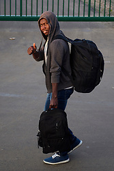 © Licensed to London News Pictures. 25/10/2016. Calais, France.  A migrant, due to leave the 'Jungle' camp, gives a thumbs up to the camera, as he carries his bags to a bus. French authorities have moved thousands of refugees and migrants living at the makeshift living area on the French coast, with some still refusing to leave. . Photo credit: Ben Cawthra/LNP