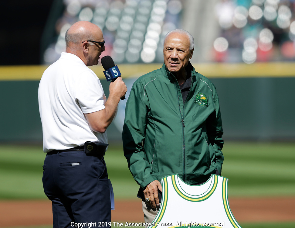 Former Seattle Supersonics broadcaster Kevin Calabro, left, interviews former Supersonics player and coach Lenny Wilkins before a Baseball game between the Seattle Mariners and the Los Angeles Angels, Saturday, June 1, 2019, in Seattle. The former NBA team was honored on the 40th anniversary of winning the NBA championship in 1979. (AP Photo/John Froschauer)